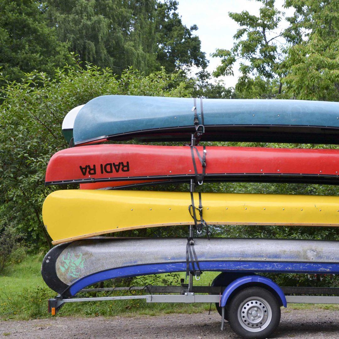 Vier bunte Kanus auf einem Autoanhänger vor grünem Hintergrund. Inklusive Sommerreise des Indiwi Berlins.