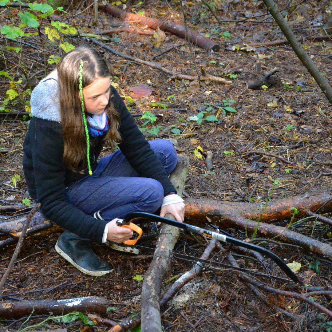 Eine Teilnehmer_in der inklusiven Herbstreise des Indiwi Berlins sitzt auf dem Waldboden und sägt mit einer Säge einen Ast durch.