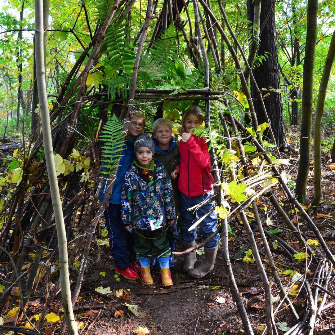 Mehrere Teilnehmer_innen der inklusiven Herbstreise des Indiwi Berlins stehen in einer Hütte, gebaut aus Ästen und Blättern.