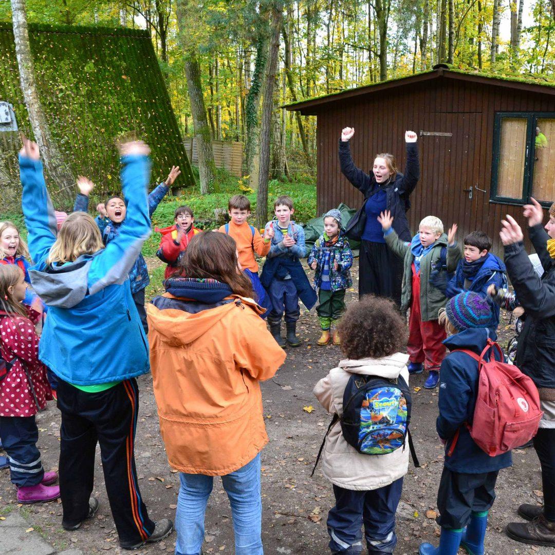 Eine Kindergruppe steht im Kreis, einige strecken die Arme nach oben. Inklusive Herbstreise des Indiwi Berlins.
