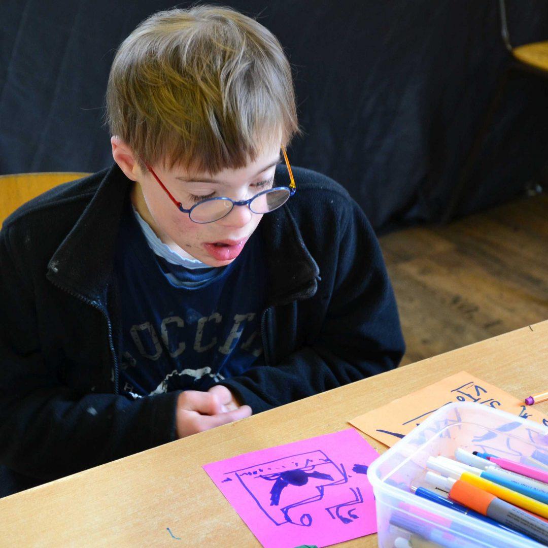 Ein Junge sitzt am Tisch. Vor ihm liegt Papier und eine Box mit Stiften. Inklusive Herbstreise des Indiwi Berlins.