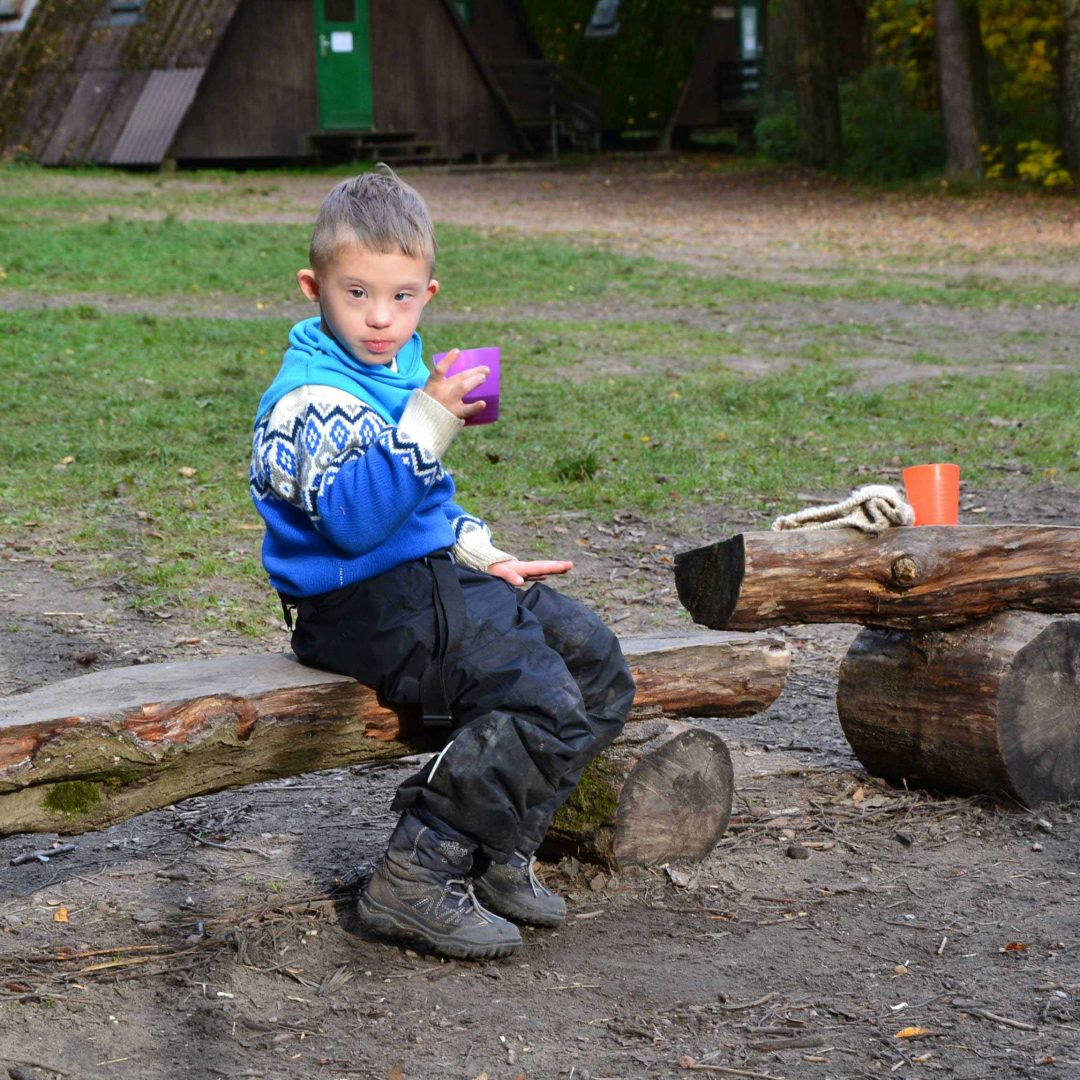 Junge sitzt auf einer Holzbank. Er hält einen Becher in der Hand. Inklusive Herbstreise des Indiwi Berlins.