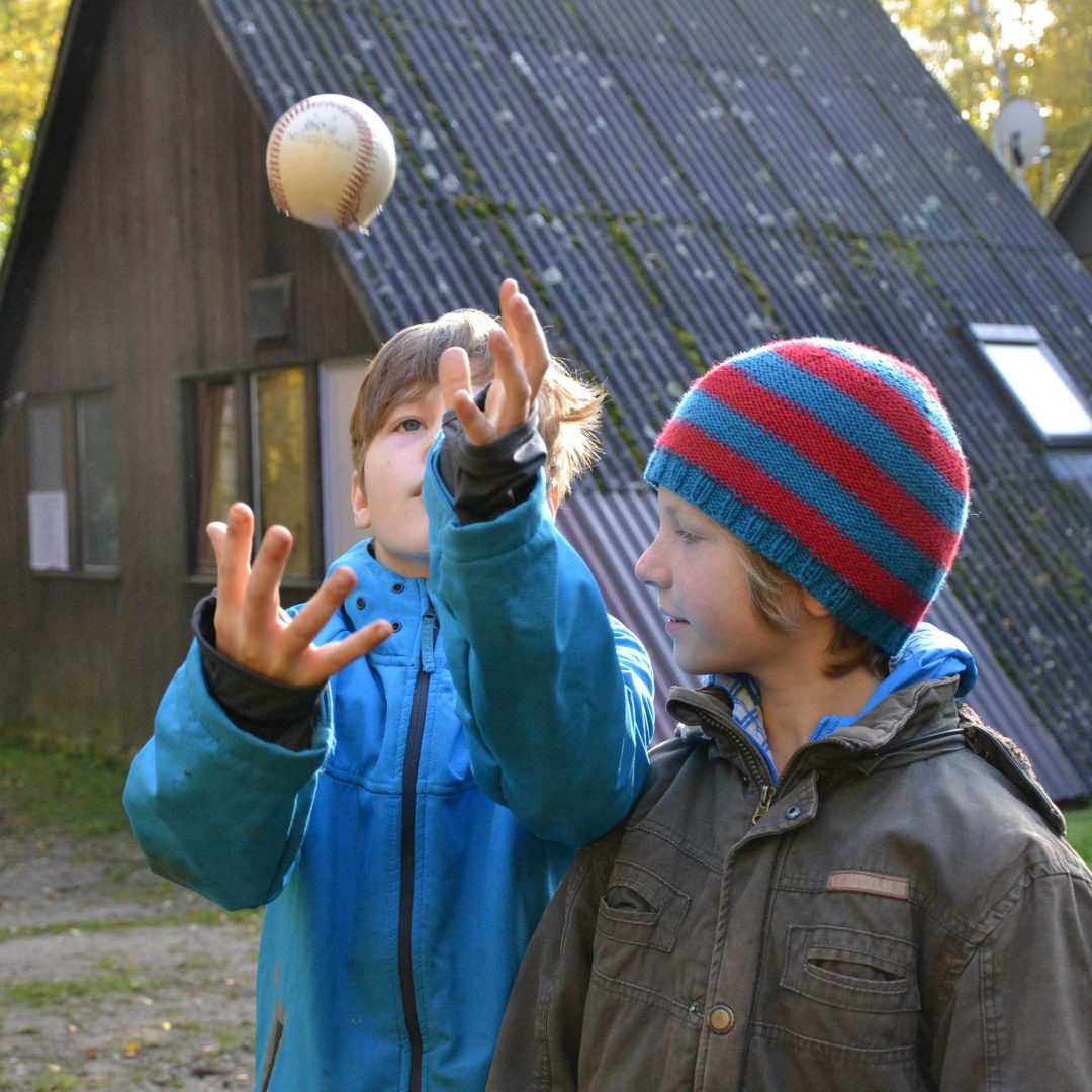 Zwei Jungen stehen nebeneinander. Ein Junge wirft einen Ball nach oben. Inklusive Herbstreise des Indiwi Berlins.