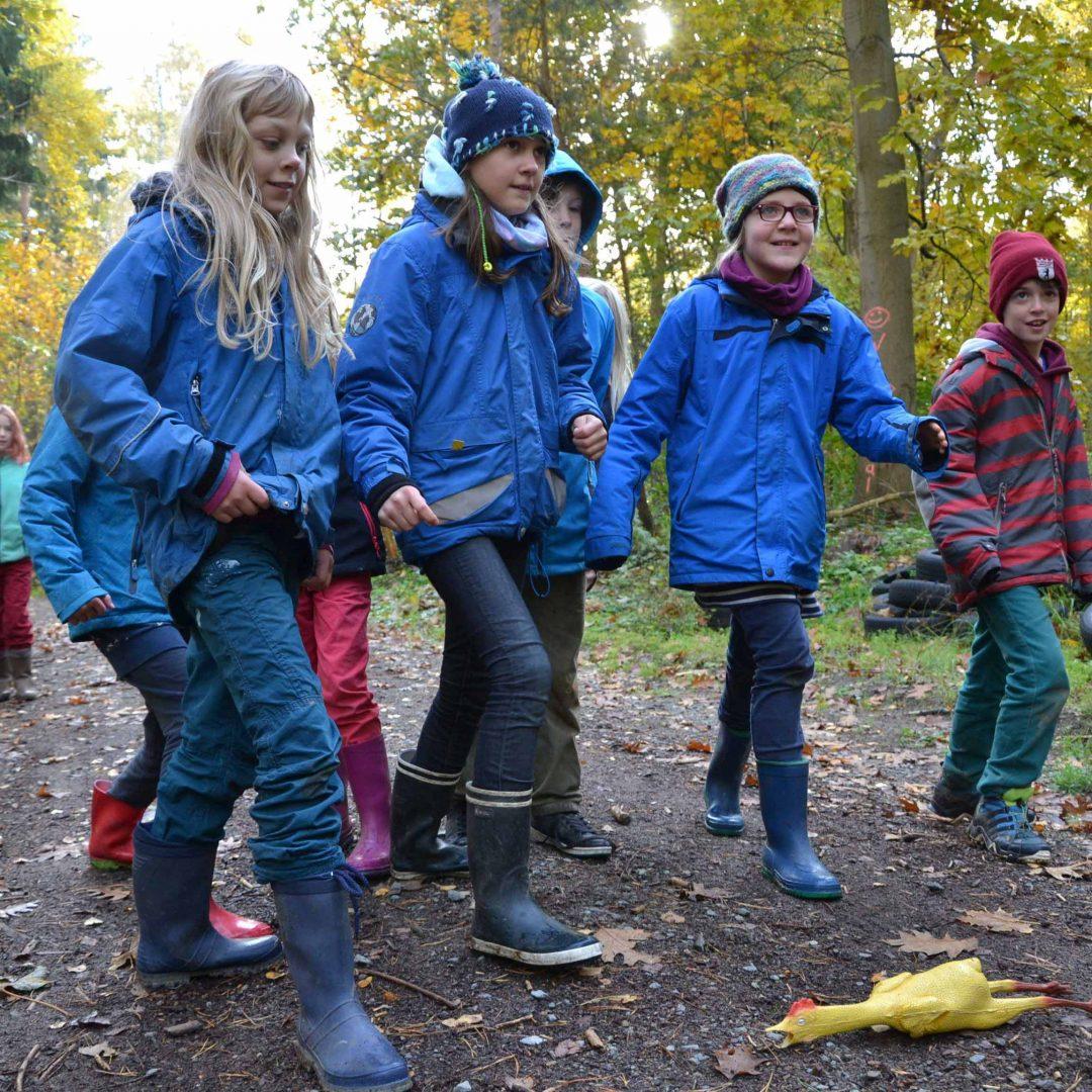 Mehrere Kinder laufen, vor ihnen liegt ein Gummihuhn auf dem Boden. Inklusive Herbstreise des Indiwi Berlins.