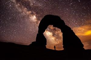 Großer Fels mit Loch, darunter steht eine Person. Sternenhimmel im Hintergrund.
