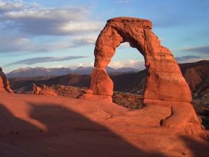 Berglandschaft. Im Vordergrund ein roter Fels im Sonnenlicht.