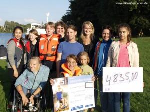 Portrait einer Gruppe (Stadtcamper des Indiwi Berlins) mit mehreren Kindern und Erwachsenen. Ein Junge hält ein Scheck.